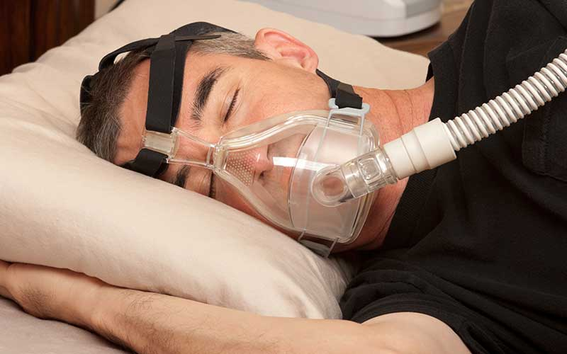 Man with obstructive sleep apnea treatment CPAP