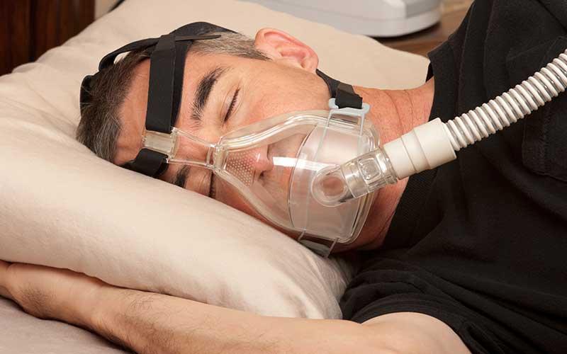 Man with obstructive sleep apnea treatment CPAP